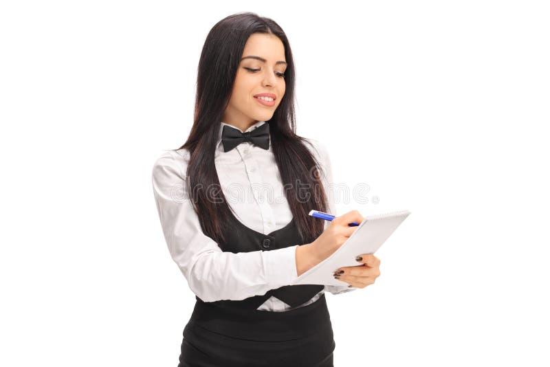 Junges Kellnerinschreiben auf einem Notizbuch stockfotos