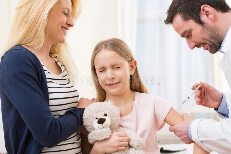 Junges kleines Mädchen begleitet von ihrer Mutter, die geimpft wird stockbilder