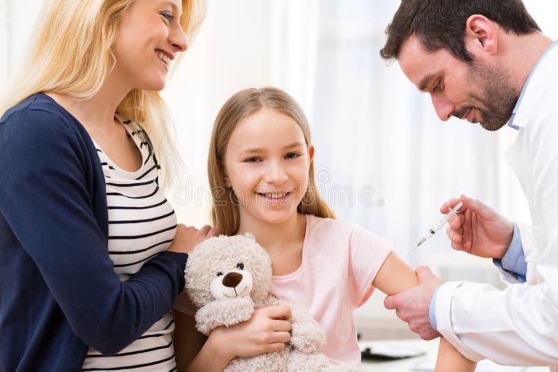 Junges kleines Mädchen begleitet von ihrer Mutter, die geimpft wird lizenzfreies stockbild