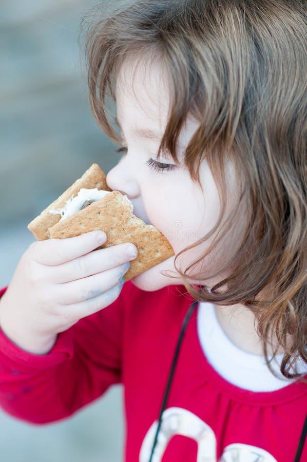 Junges kleines Mädchen isst ein s-` machte mehr von Graham-Crackern, von gebratenen Eibischen und von der Schokolade Ihr Mund ist stockfotografie