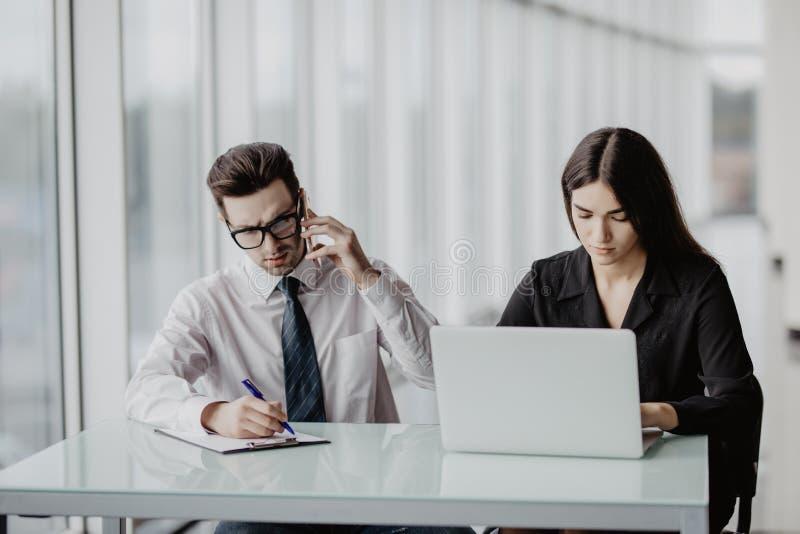 Junges kreatives Teambrainstorming im Büro Hübscher männlicher Geschäftsmann, der Anruf während lächelnder Assistent sitzt nahe b stockfotos