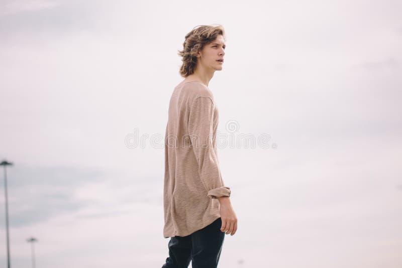 Junges Lächeln des gutaussehenden Mannes im Freien auf Himmelhintergrund stockfotografie