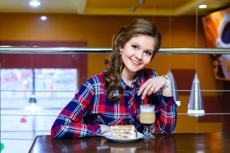 Junges lächelndes Mädchen, das im Café mit einer Schale mokachino sitzt und lizenzfreies stockbild