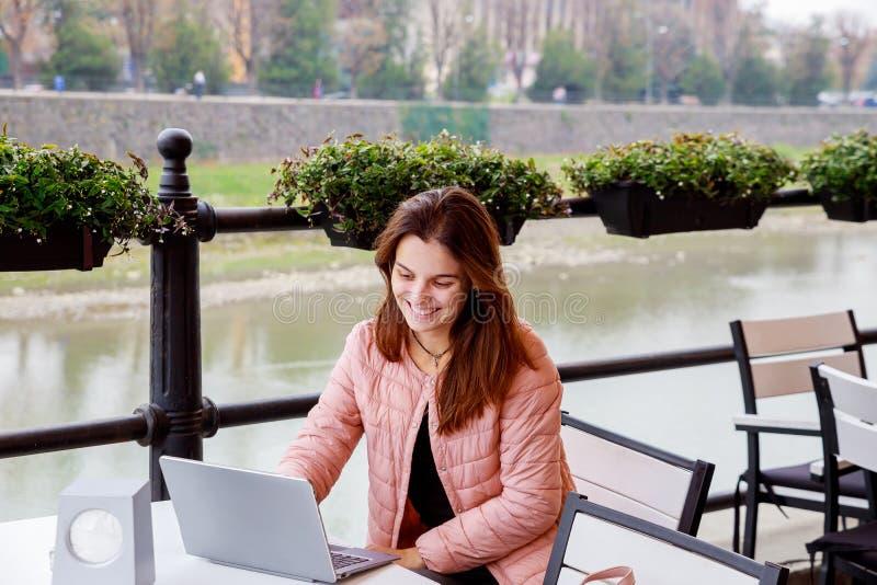 Junges lächelndes Mädchen, das Laptop für Arbeit beim Sitzen Café am im Freien, Student studiert am Park und verwendet modernen L stockbild