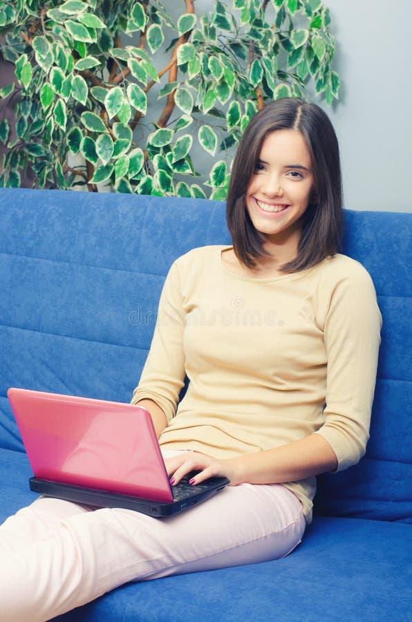 Junges lächelndes Mädchen, das Notizbuch beim auf Couch zu Hause sitzen verwendet stockbild