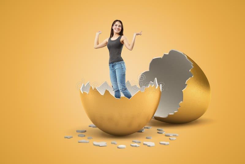 Junges lächelndes Mädchen in der grauen ärmellosen Spitze und in den Blue Jeans hat gerade heraus vom goldenen Ei ausgebrütet und lizenzfreie stockfotos