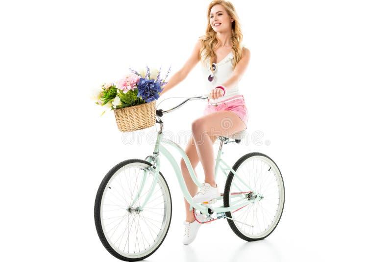 Junges lächelndes Mädchenreitfahrrad mit Blumen im Korb lizenzfreies stockbild