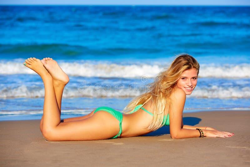 Junges Lügen des blonden Bikinimädchens auf dem Strandsand stockfoto