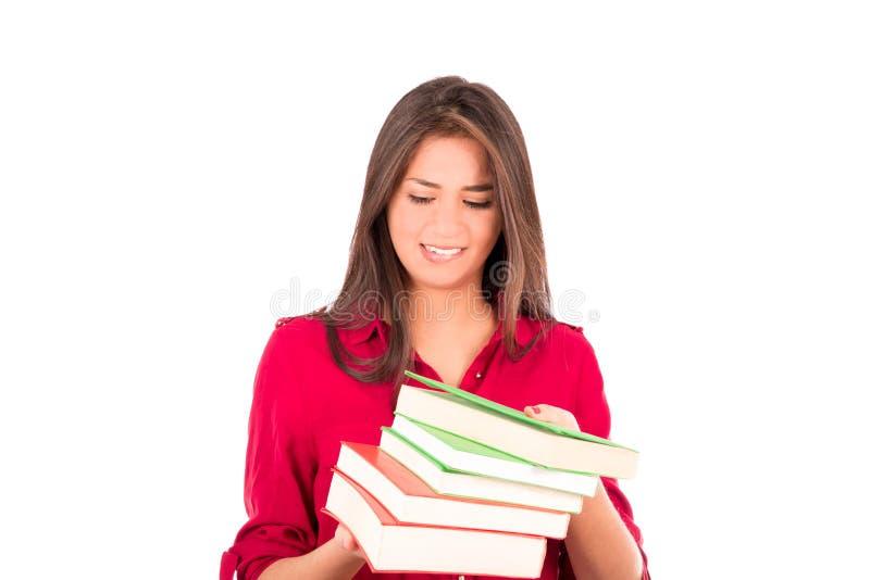 Junges lateinisches Mädchen, das Stapel von Büchern hält stockbild