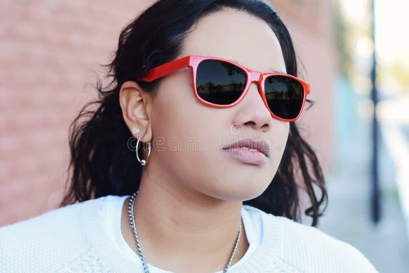Junges lateinisches Mädchen in der roten Sonnenbrille lizenzfreies stockfoto