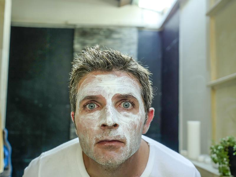 Junges lustiges attraktives Badezimmer des Mannes zu Hause, das den Toilettenspiegel anwendet facemask in seinem Gesicht sich fin stockbild