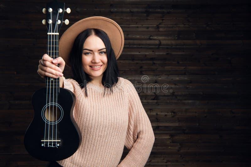 Junges lustiges Hippie-Mädchen, das Spaß hat und auf kleiner Ukulelegitarre, -gesang und -c$tanzen spielt tragender Weinlesehut,  stockfoto