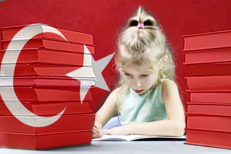 Junges Mädchen mit dem weißen Haar möchte Türkisch lernen hinter ihrer Flagge auf dem Tisch ein Stapel von Büchern lizenzfreie stockfotografie