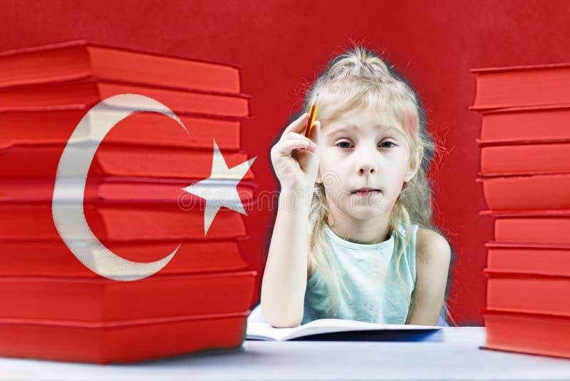 Junges Mädchen mit dem weißen Haar möchte Türkisch lernen hinter ihrer Flagge auf dem Tisch ein Stapel von Büchern stockfotos