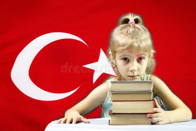Junges Mädchen mit dem weißen Haar möchte Türkisch lernen hinter ihrer Flagge auf dem Tisch ein Stapel von Büchern stockfotografie