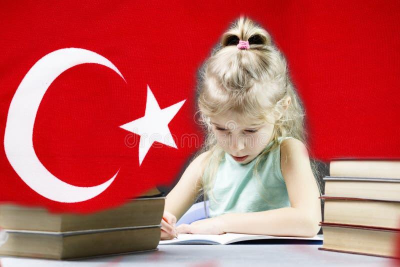 Junges Mädchen mit dem weißen Haar möchte Türkisch lernen hinter ihrer Flagge auf dem Tisch ein Stapel von Büchern stockbilder