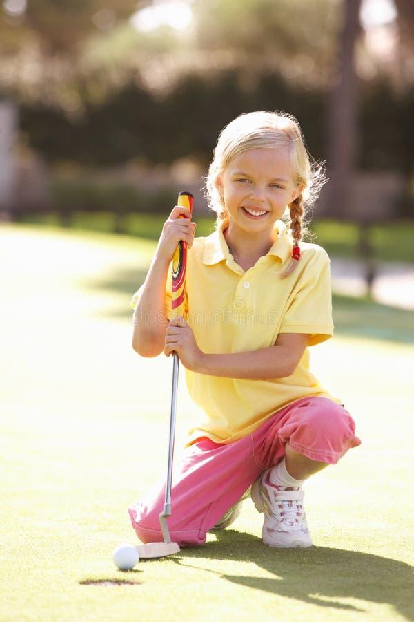 Junges Mädchen-übendes Golf stockbild