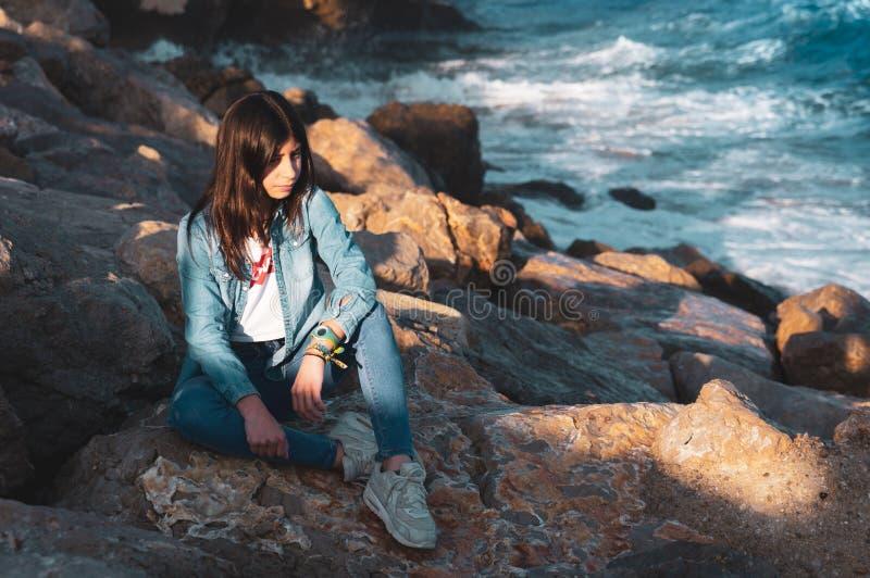 Junges Mädchen allein, das auf Felsen durch das Meer in entspannter Haltung sitzt stockfoto