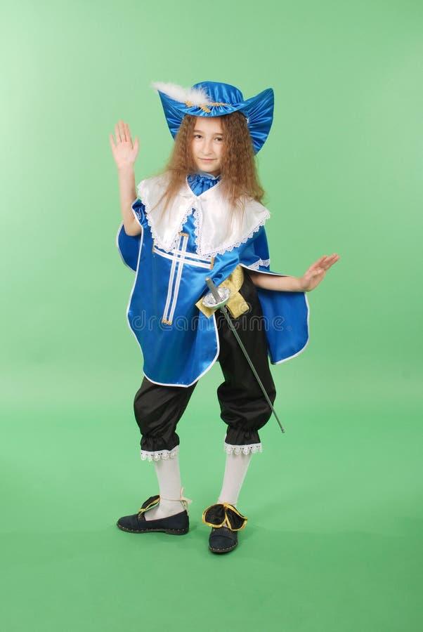 Junges Mädchen als Musketier im blauen Kostüm mit reizendem blauem Hut mit Federn stockfotos