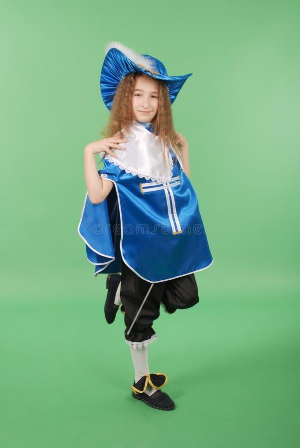 Junges Mädchen als Musketier im blauen Kostüm mit reizendem blauem Hut mit Federn lizenzfreie stockfotos