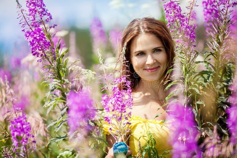 Junges Mädchen auf dem Gebiet mit lila Blumen stockbild