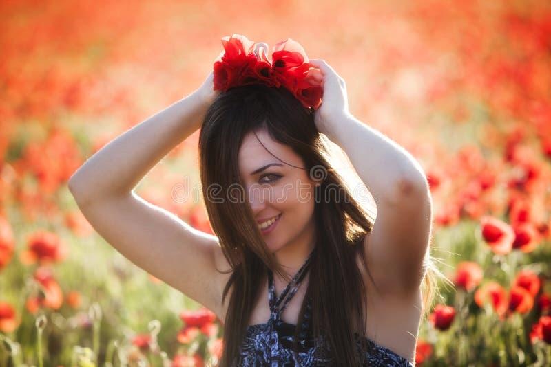 Junges Mädchen auf dem Mohnblumengebiet lizenzfreies stockfoto