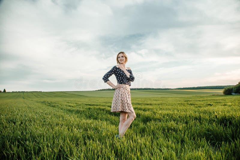 Junges Mädchen auf einem grünen Gebiet Stilvolles Mädchen Grünes Gras und blauer Himmel Emotionale Frau plener Reise reise stockfotos