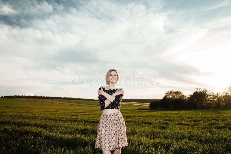 Junges Mädchen auf einem grünen Gebiet Stilvolles Mädchen Grünes Gras und blauer Himmel Emotionale Frau plener Reise reise lizenzfreie stockfotos