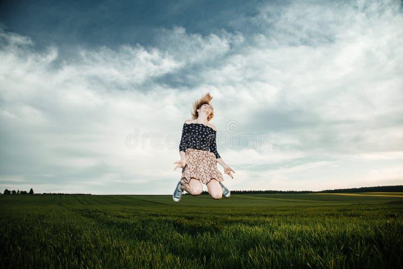 Junges Mädchen auf einem grünen Gebiet Stilvolles Mädchen Grünes Gras und blauer Himmel Emotionale Frau plener Reise reise stockbild