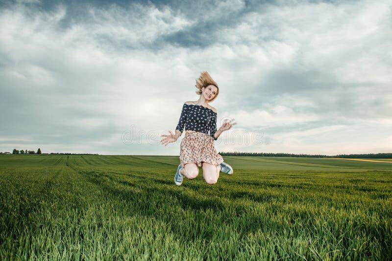 Junges Mädchen auf einem grünen Gebiet Stilvolles Mädchen Grünes Gras und blauer Himmel Emotionale Frau plener Reise reise stockfotografie
