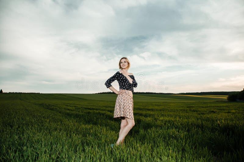 Junges Mädchen auf einem grünen Gebiet Stilvolles Mädchen Grünes Gras und blauer Himmel Emotionale Frau plener Reise reise stockfoto