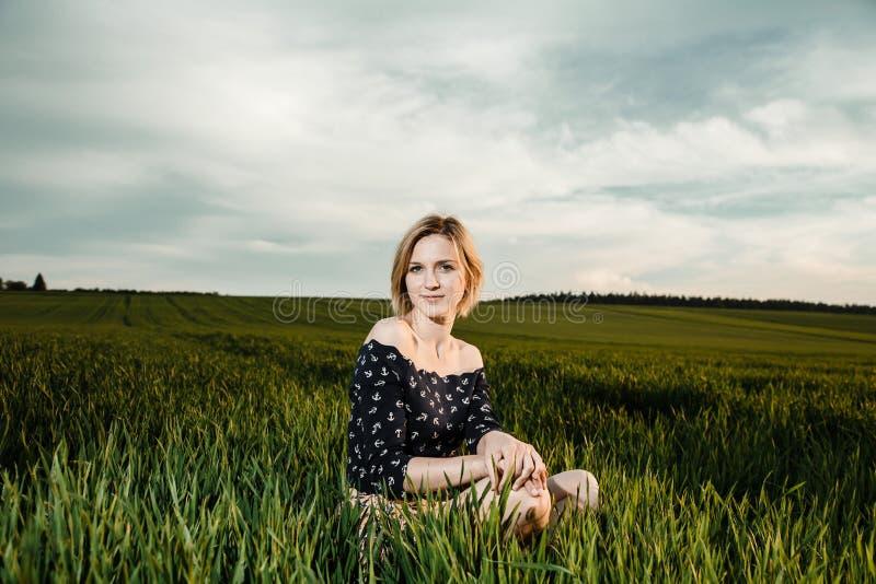 Junges Mädchen auf einem grünen Gebiet Stilvolles Mädchen Grünes Gras und blauer Himmel Emotionale Frau plener Reise reise lizenzfreie stockbilder