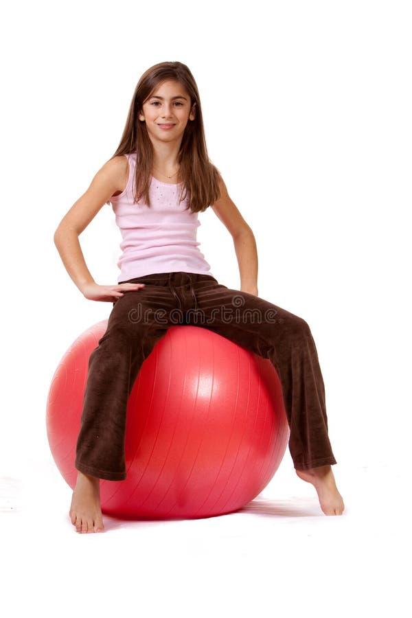 Junges Mädchen auf einer Übungs-Kugel lizenzfreies stockfoto