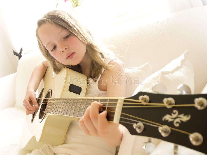 Junges Mädchen auf einer Akustikgitarre 4 lizenzfreie stockfotos