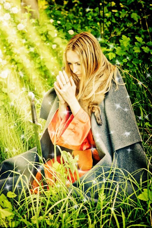 Junges Mädchen auf ihren Knien betend im Holz lizenzfreies stockfoto