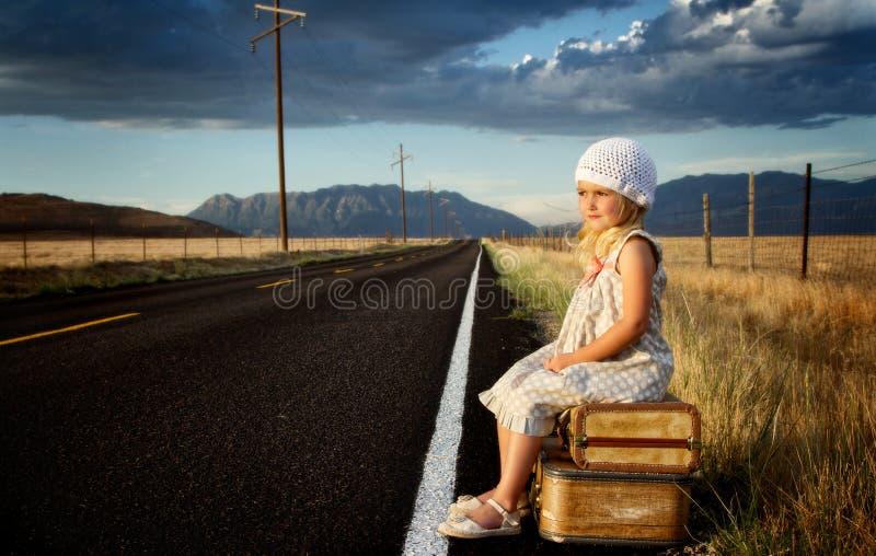Junges Mädchen auf Seite der Straße mit Koffern lizenzfreies stockfoto