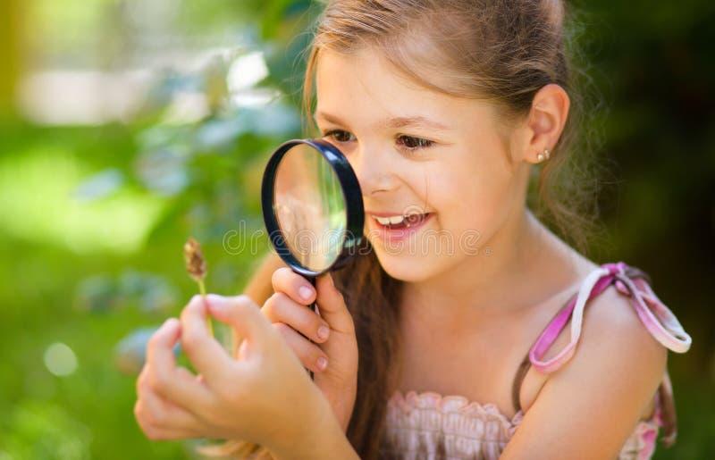 Junges Mädchen betrachtet Blume durch Vergrößerungsglas lizenzfreie stockbilder