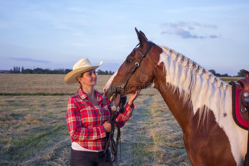 Junges Mädchen betrachtet ihr Pferd im Gras stockfoto