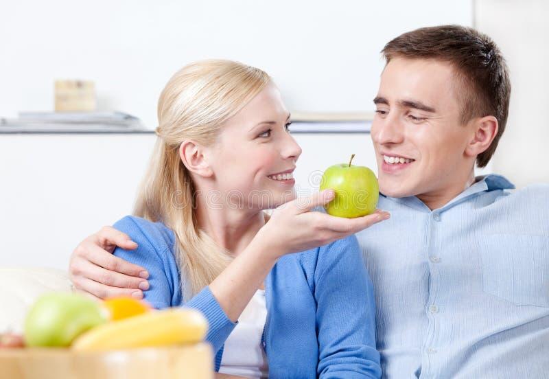 Junges Mädchen bietet einen Apfel ihrem Ehemann an stockfotos