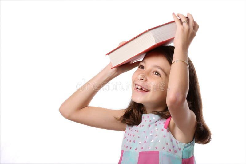 Junges Mädchen-Bilanzbuch auf Kopf stockbild