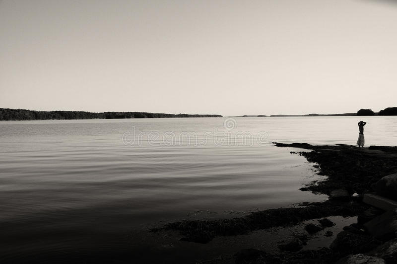 Junges Mädchen, das über ruhigem Wasser schaut stockfotografie