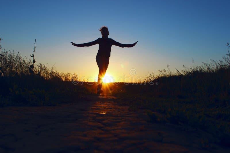 Junges Mädchen, das über Sonnenuntergang-Hintergrund springt Schattenbild in voller Länge eines glücklichen Mädchens, das draußen lizenzfreie stockbilder