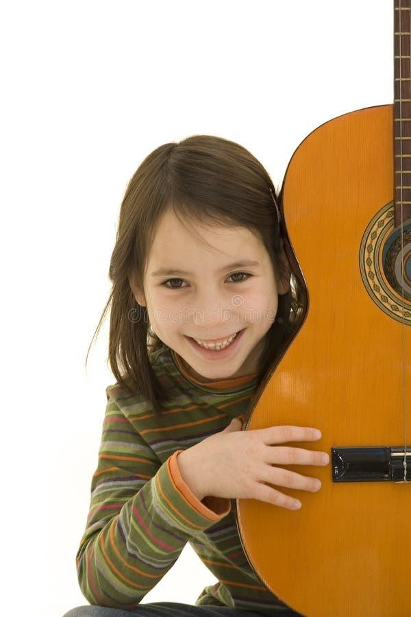 Junges Mädchen, das Akustikgitarre spielt stockfotografie