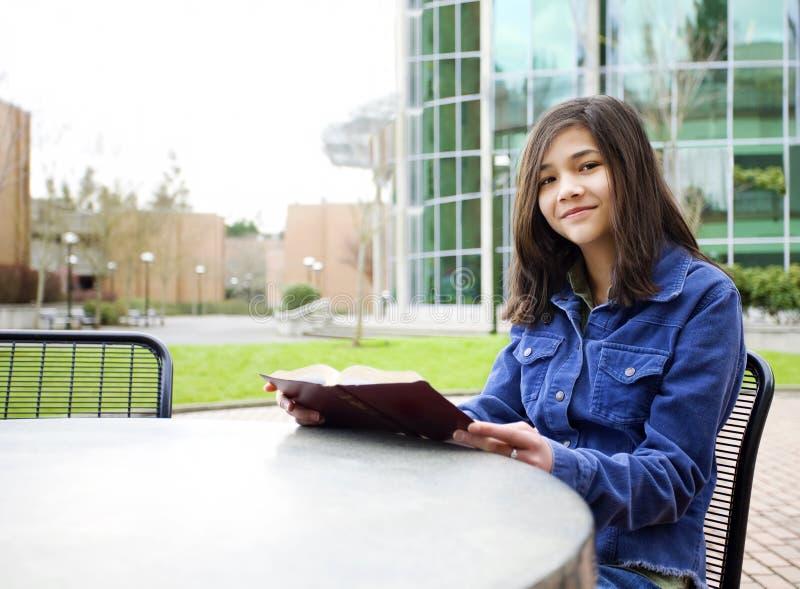 Junges Mädchen, das außerhalb des Lesens eines Buches sitzt lizenzfreie stockfotos