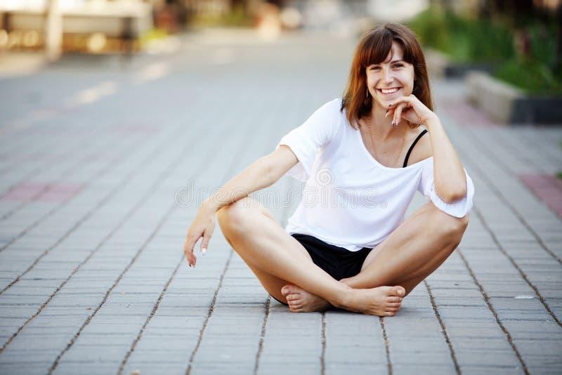 Junges Mädchen, das auf Asphalt sitzt lizenzfreie stockfotografie