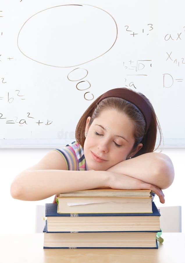 Junges Mädchen, das auf Büchern an der Schule schläft stockfoto