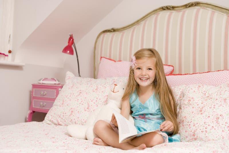 Junges Mädchen, das auf Bett mit dem Buchlächeln sitzt lizenzfreie stockbilder