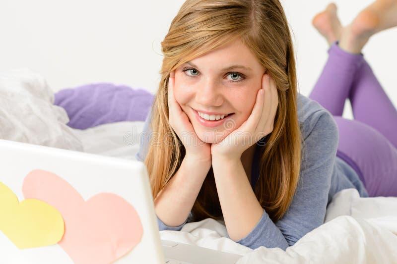 Junges Mädchen, das auf Bett mit Laptop liegt stockfotografie