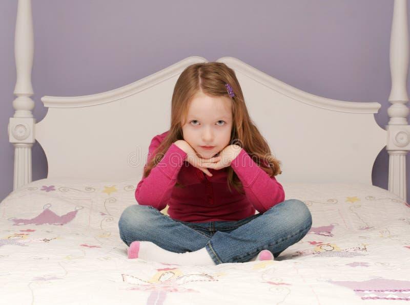 Junges Mädchen, das auf Bett sitzt lizenzfreie stockbilder