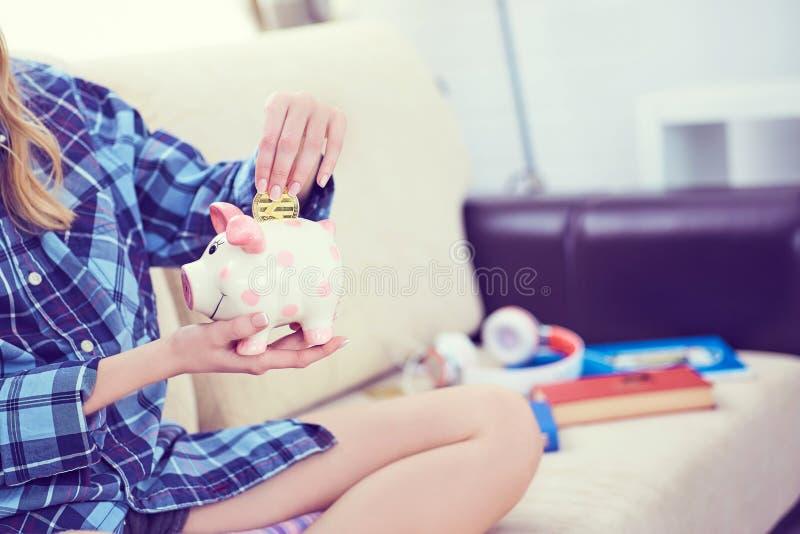Junges Mädchen, das auf Couch sitzt und litecoin in piggybank einsetzt lizenzfreie stockfotografie